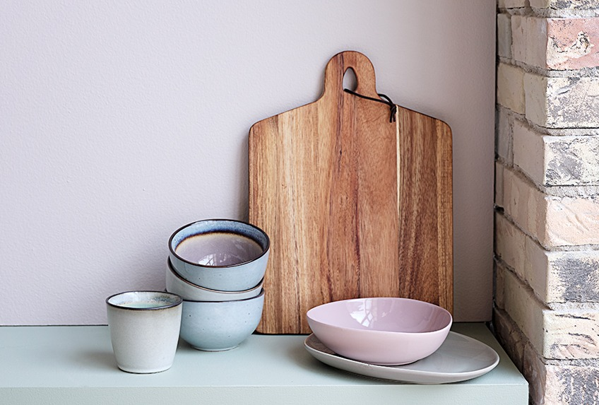 Table with bowls, plates, cups and cutting board