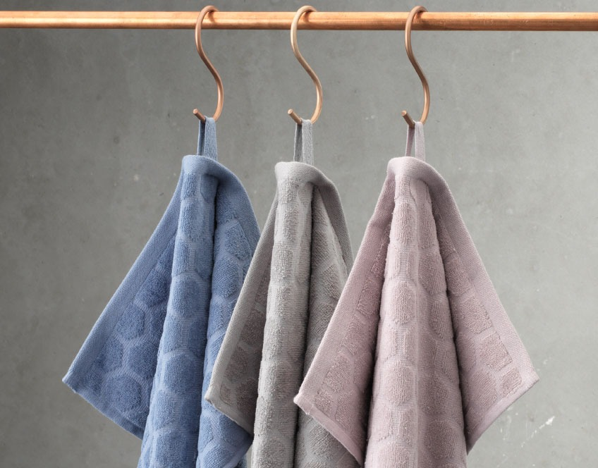 Hand towels in three colours hanging from a rail