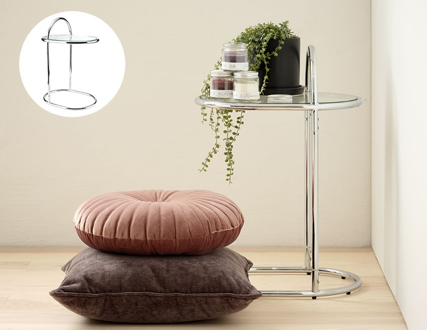 A chrome side table with a plant pot in a corner and two cushions on the floor